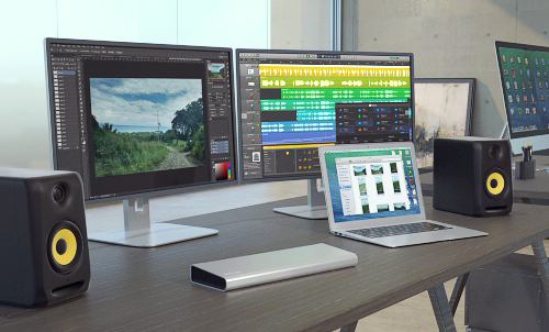 Imagen del replicador de puertos Thunderbolt 2 de vídeo doble, desplegado en un estudio creativo, y conectado a unos parlantes de audio digital óptico