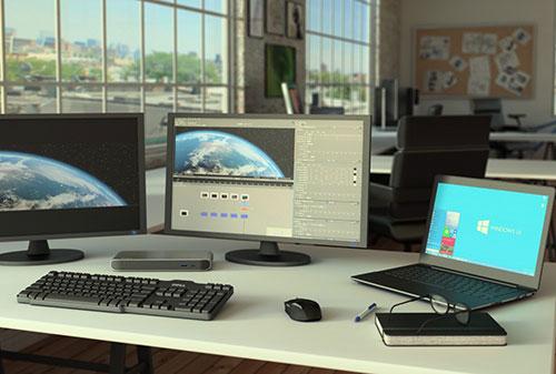 Imagen del replicador de puertos Thunderbolt 3 conectado a una estación de trabajo con monitor 4K dual, en un entorno de estudio creativo