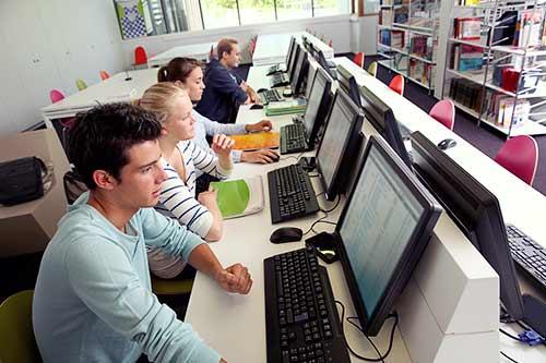 Imagen que muestra estudiantes en un entorno de laboratorio informático y aula de clase. Este replicador de puertos para ordenador portátil con doble anfitrión resulta perfecto para entornos educativos y colaborativos.