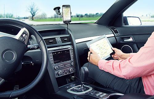 Mientras se carga un smartphone Samsung en el conector para teléfono del coche, se carga el iPad de uno de los pasajeros