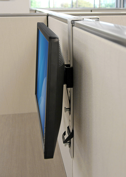 A side view of a monitor hanging over a cubicle wall using the ARMCBCL