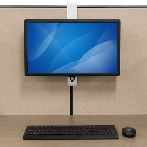 A monitor hanging over a cubicle wall using the ARMCBCL at a desk with a keyboard and mouse