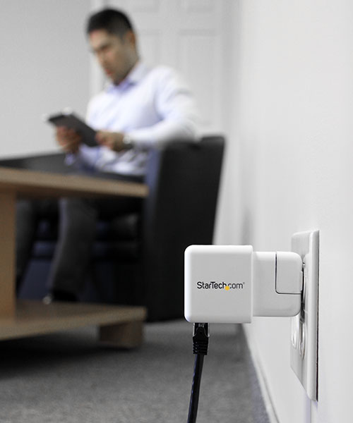 Image of travel router plugged into wall power adapter with Ethernet network connected