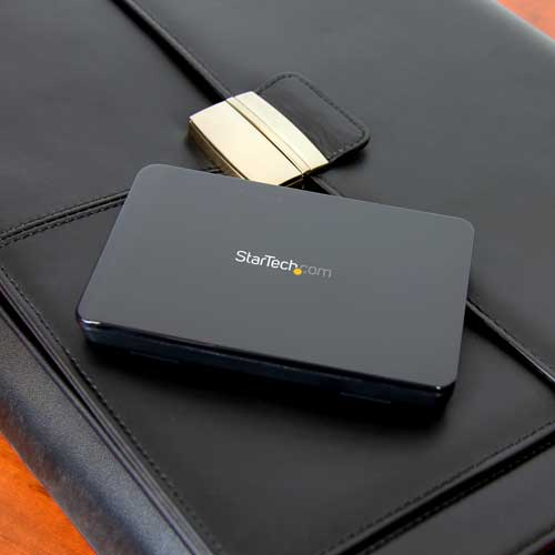 Photo of StarTech.com USB 3.1 Gen 2 enclosure (S251BPU313) on laptop bag showing easy portability