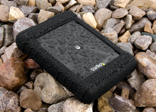 Rugged enclosure sitting outdoors on a rock bed in the rain
