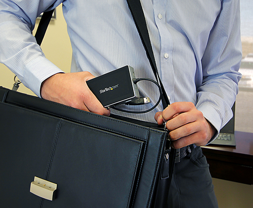 Business professional tucking the travel docking station into a laptop bag